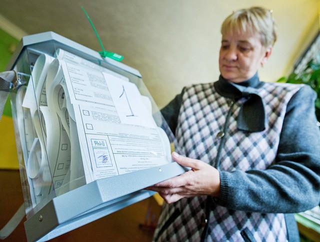 Работник избирательного участка держит урну для голосования