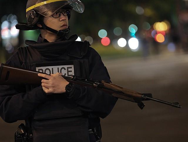 Сотрудник полиции стоит в оцеплении на месте перестрелки в Париже
