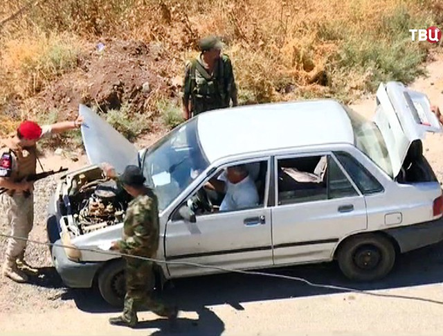 Военная полиция МО России осматривает машину на КПП в Сирии