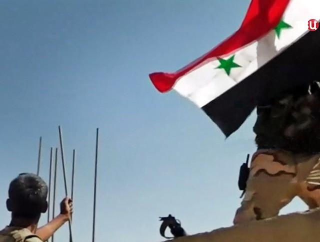 Военнослужащие армии Сирии поднимают флаг