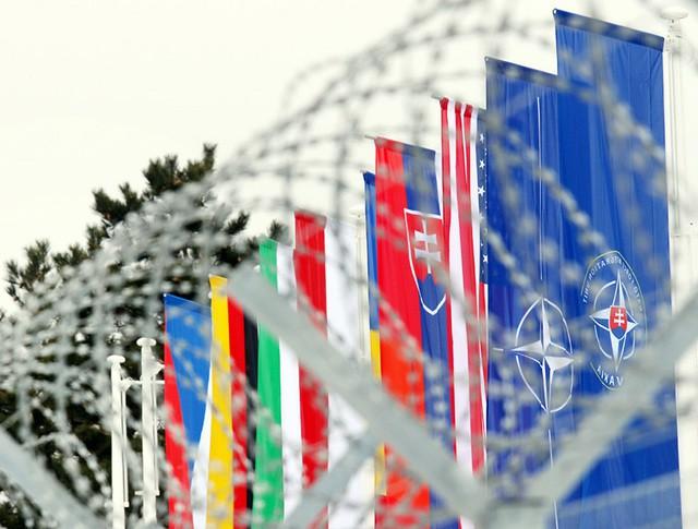 Флаги стран НАТО за колючей проволокой