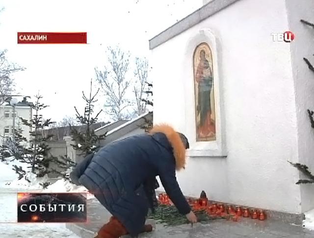 Прихожане приносят цветы и свечи к храму