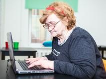 Пожилая женщина работает на компьютере