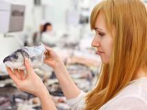 Девушка выбирает рыбу в супермаркете