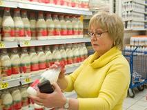 Женщина проверяет срок годности молока