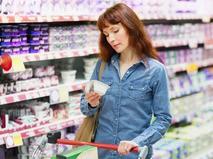 Женщина выбирает творог в магазине