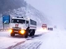 Сотрудники МЧС работают во время снегопада на трассе