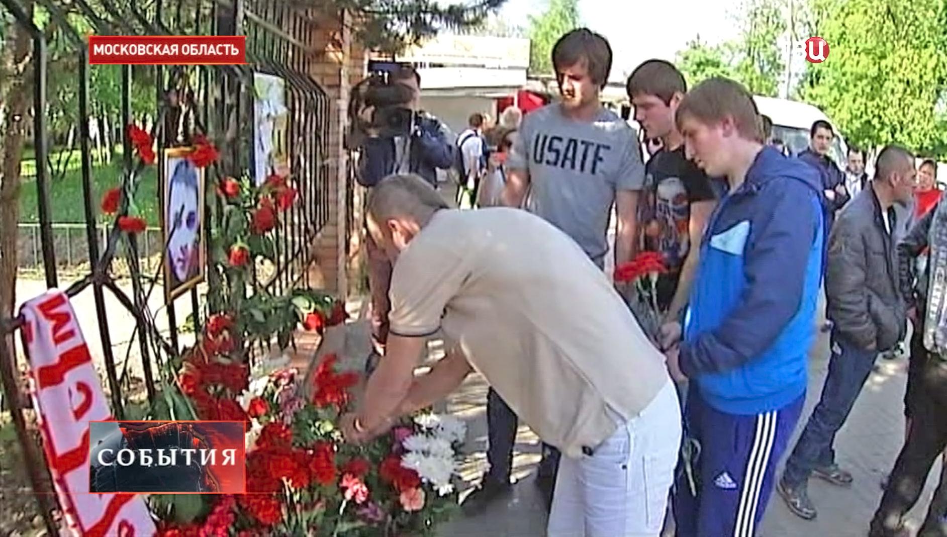Футбольные болельщики приносят цветы на место трагедии