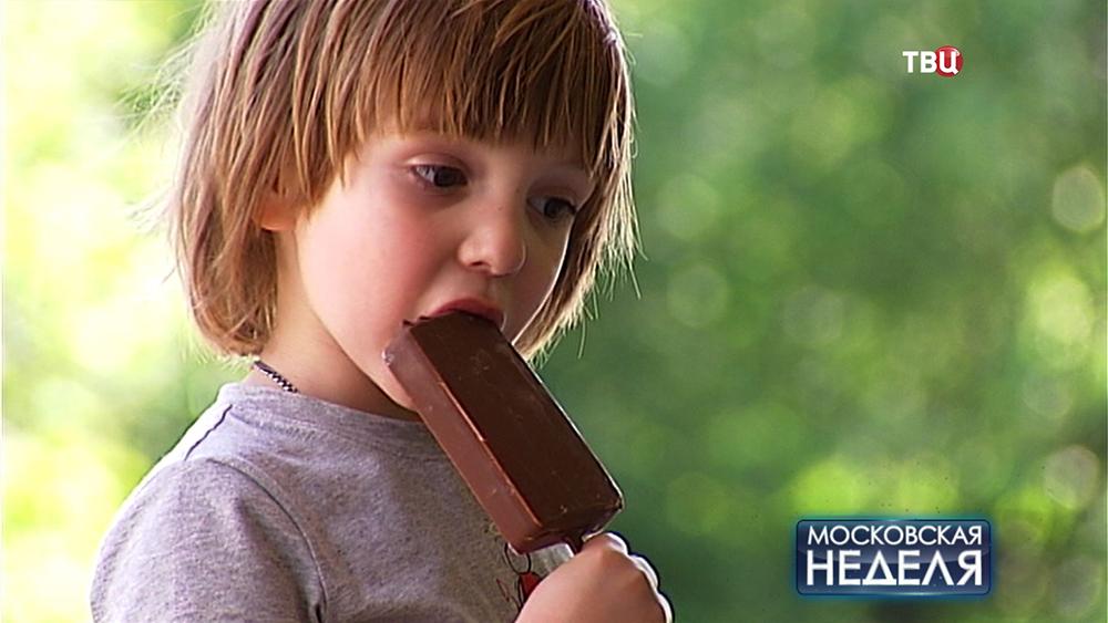 Мальчик ест мороженое