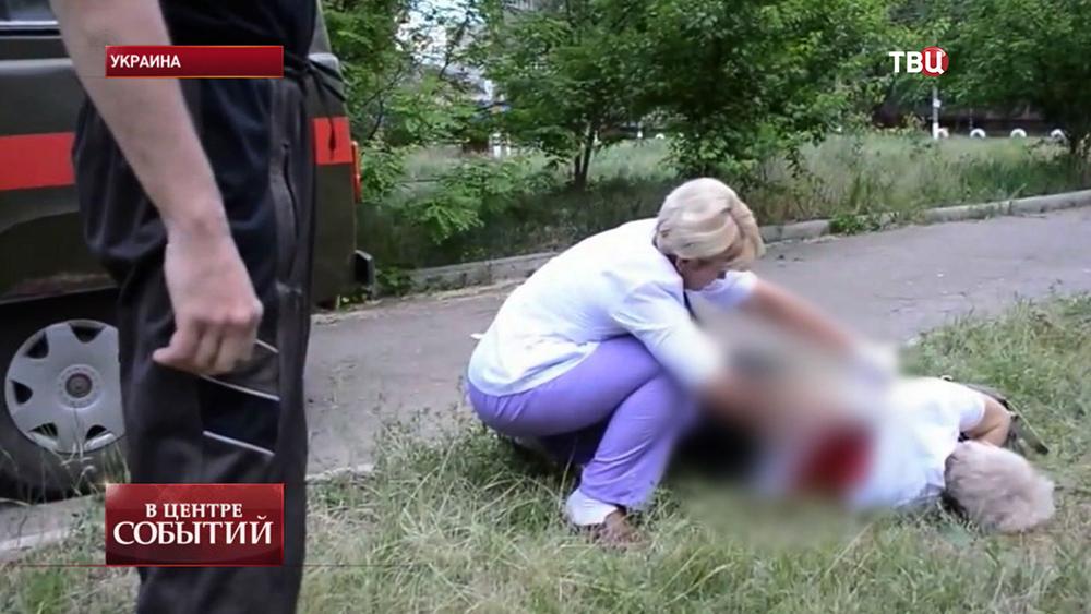 Врач осматривает погибшего при обстреле Донецка