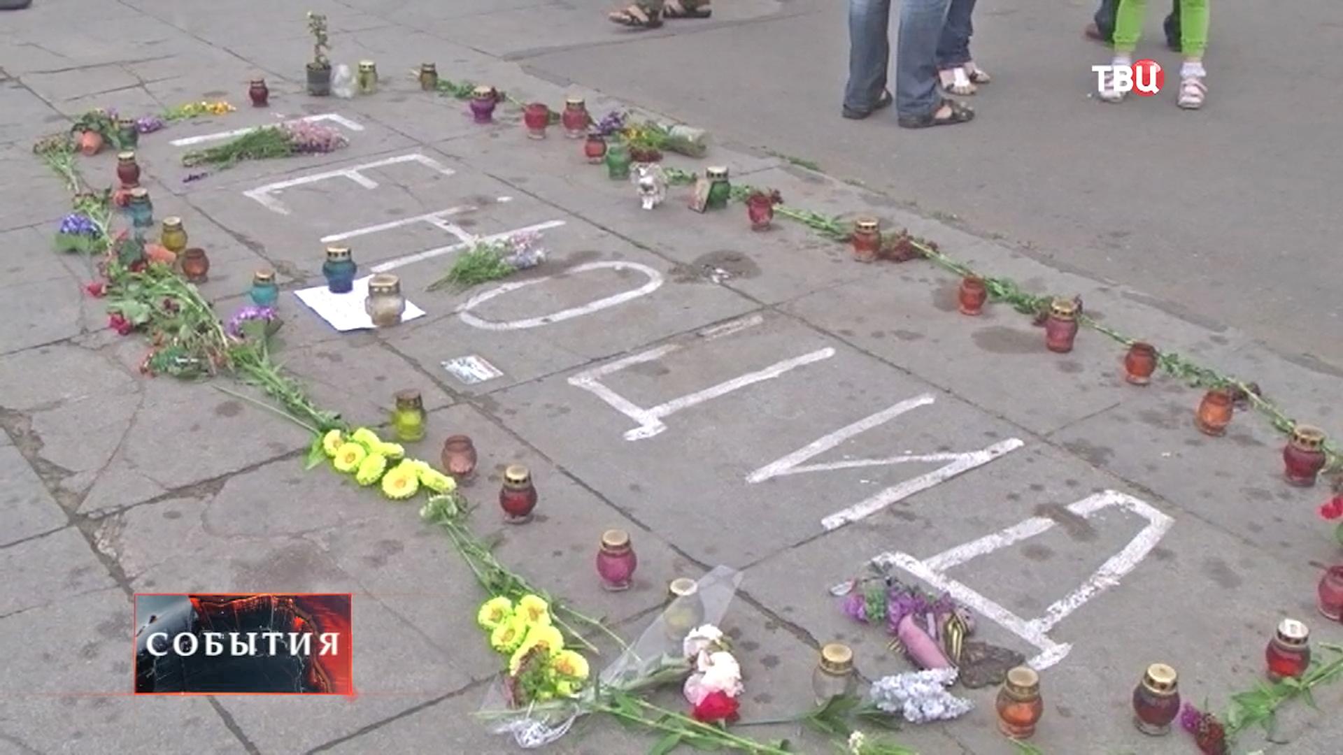 Люди приносят свечи и цветы в память о погибших