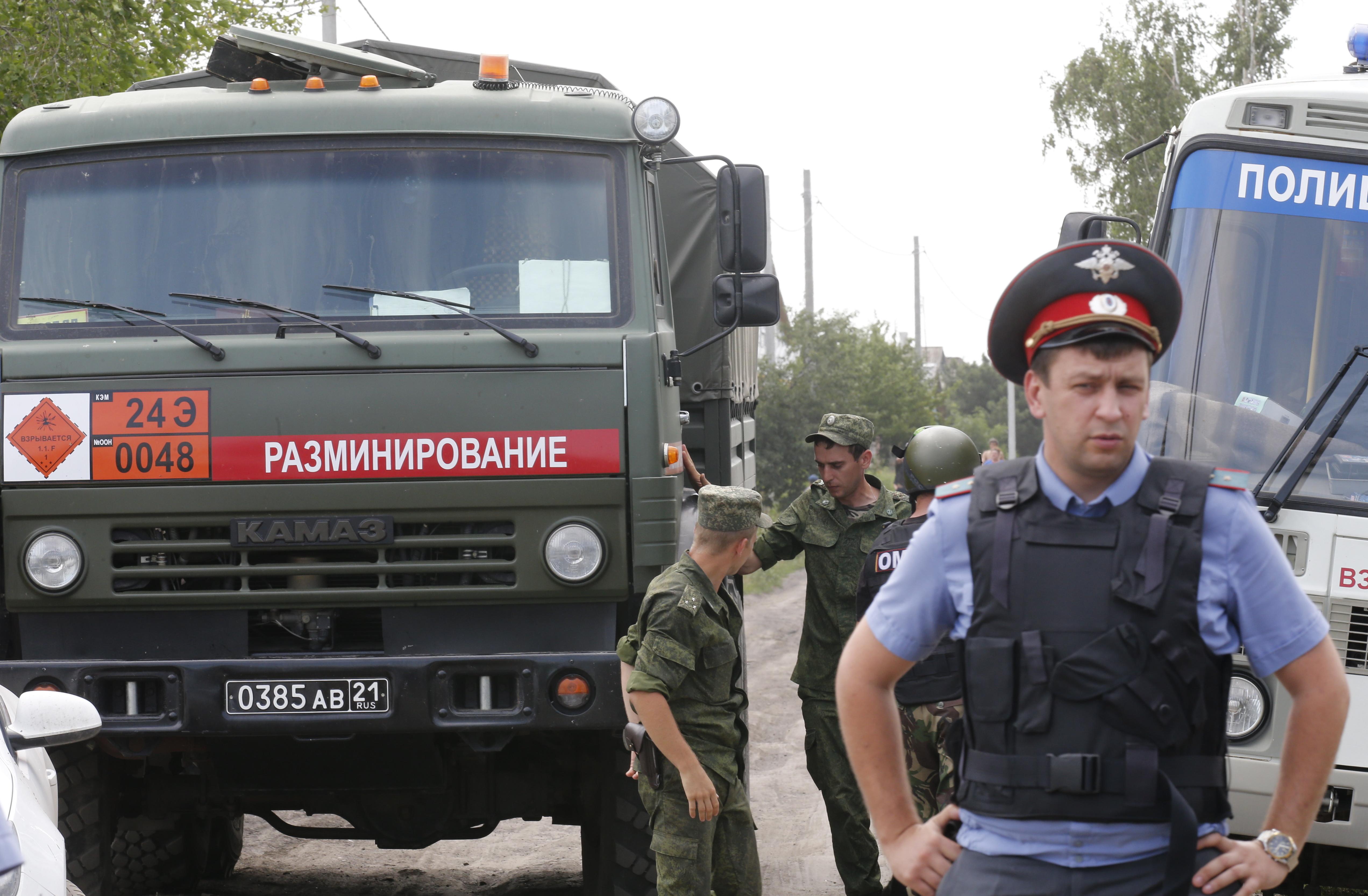 Сотрудники полиции у жилого дома в российском Донецке, во дворе которого разорвался снаряд украинской армии