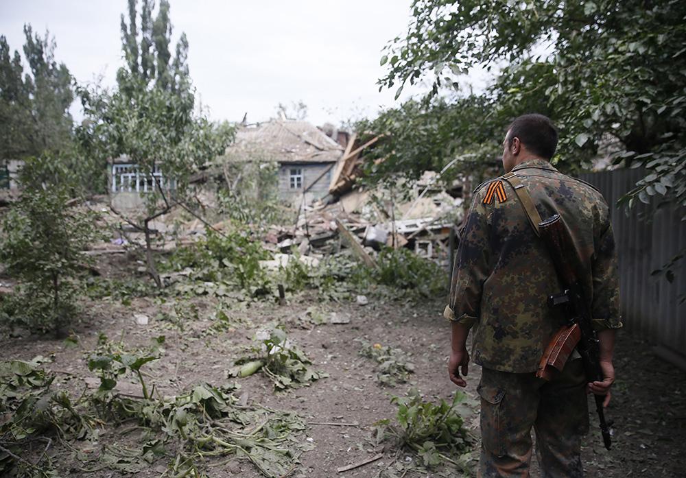 Народный ополченец на месте разрушенного в результате авиаудара жилого дома