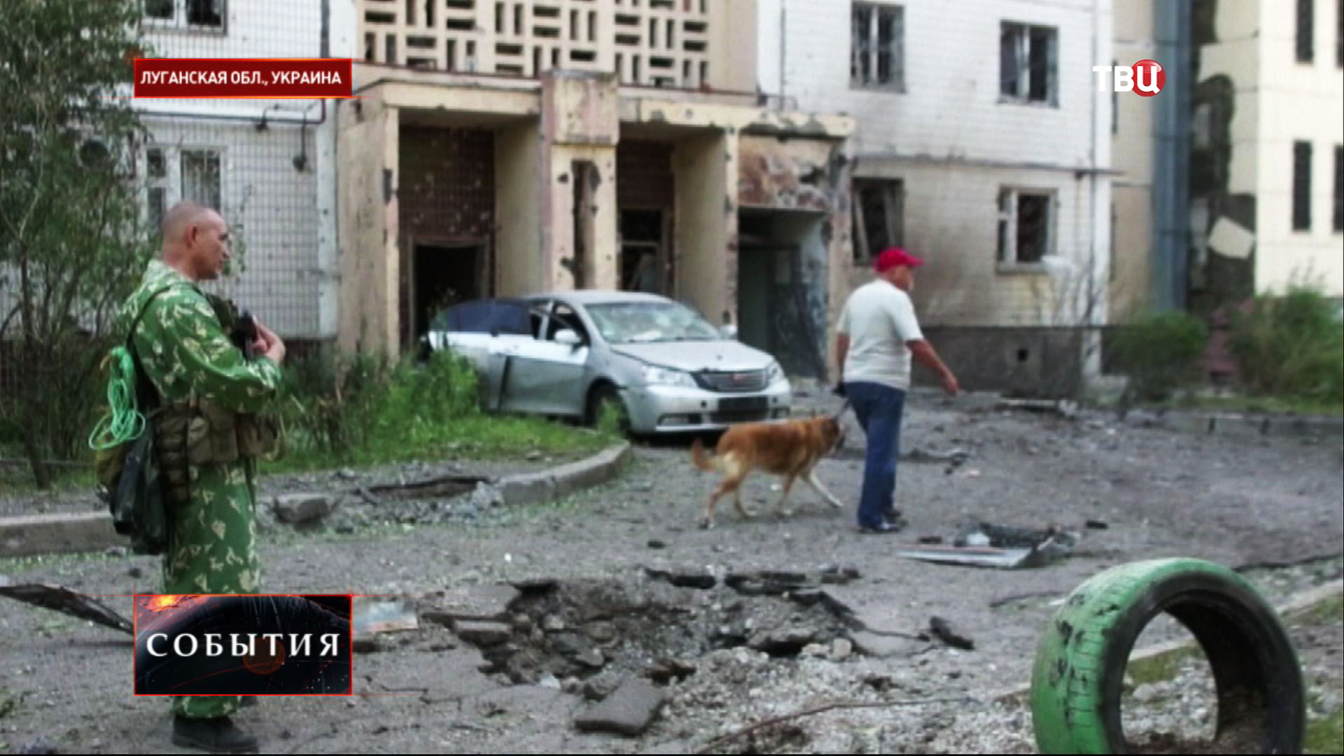 Народный ополченец у жилого дома, поврежденного в результате артобстрела украинскими военными