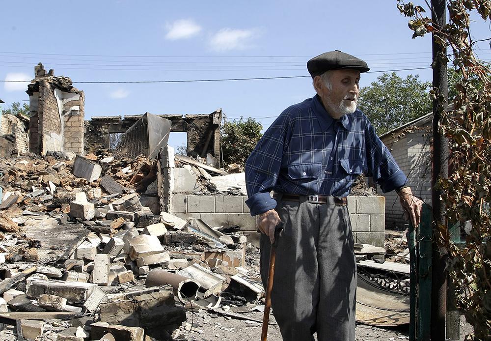 Местный житель у дома, разрушенного в результате боевых действий между украинской армией и ополчением ДНР