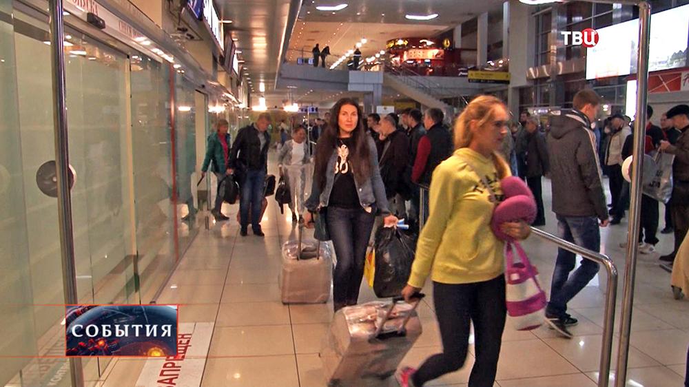 Пассажиры в зале прилета в аэропорте