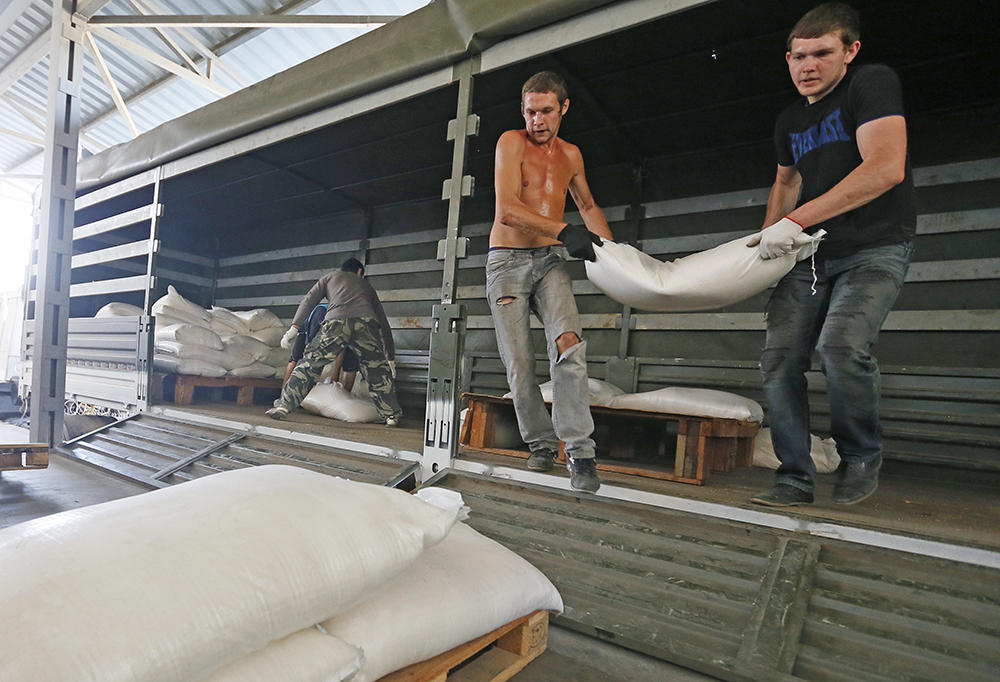 Разгрузка грузовиков конвоя с гуманитарной помощью для жителей юго-востока Украины