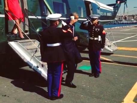 Президент США Барак Обама отдаёт честь с кофе в руке