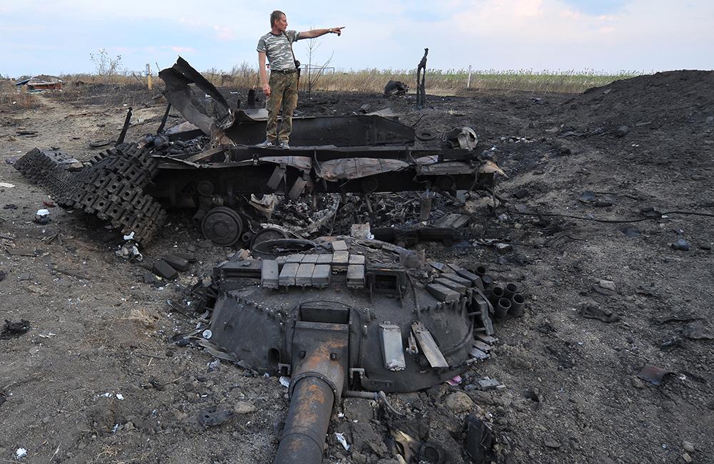 Народный ополченец Донбасса около сгоревшего танка украинских войск