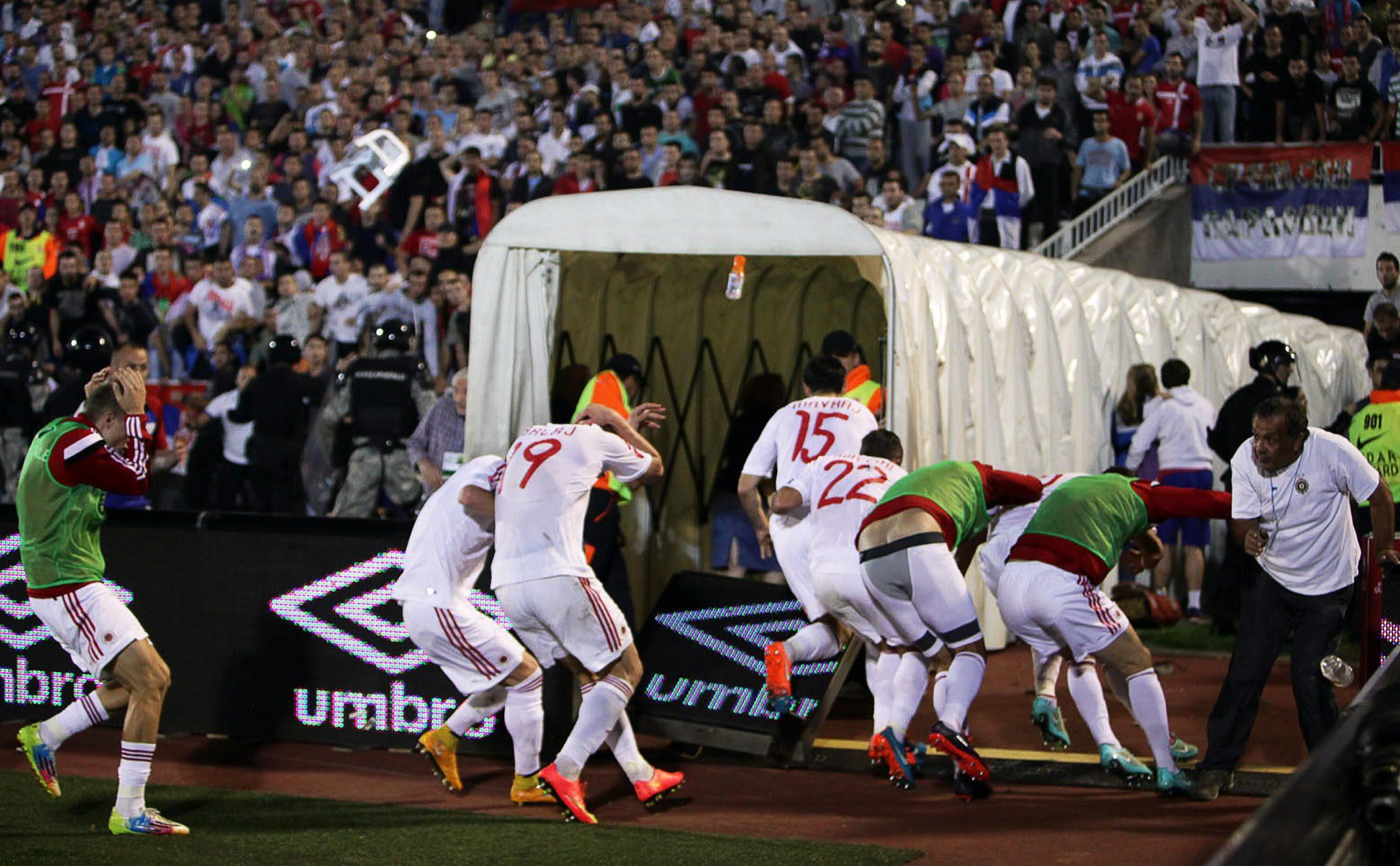 Футболисты сборной Албании бегут с поля от болельщиков сборной Сербии