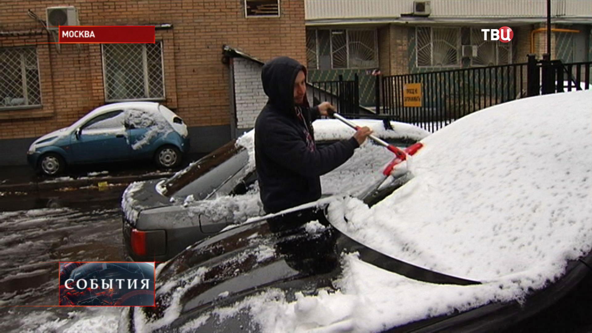 Мужчина чистит машину от снега