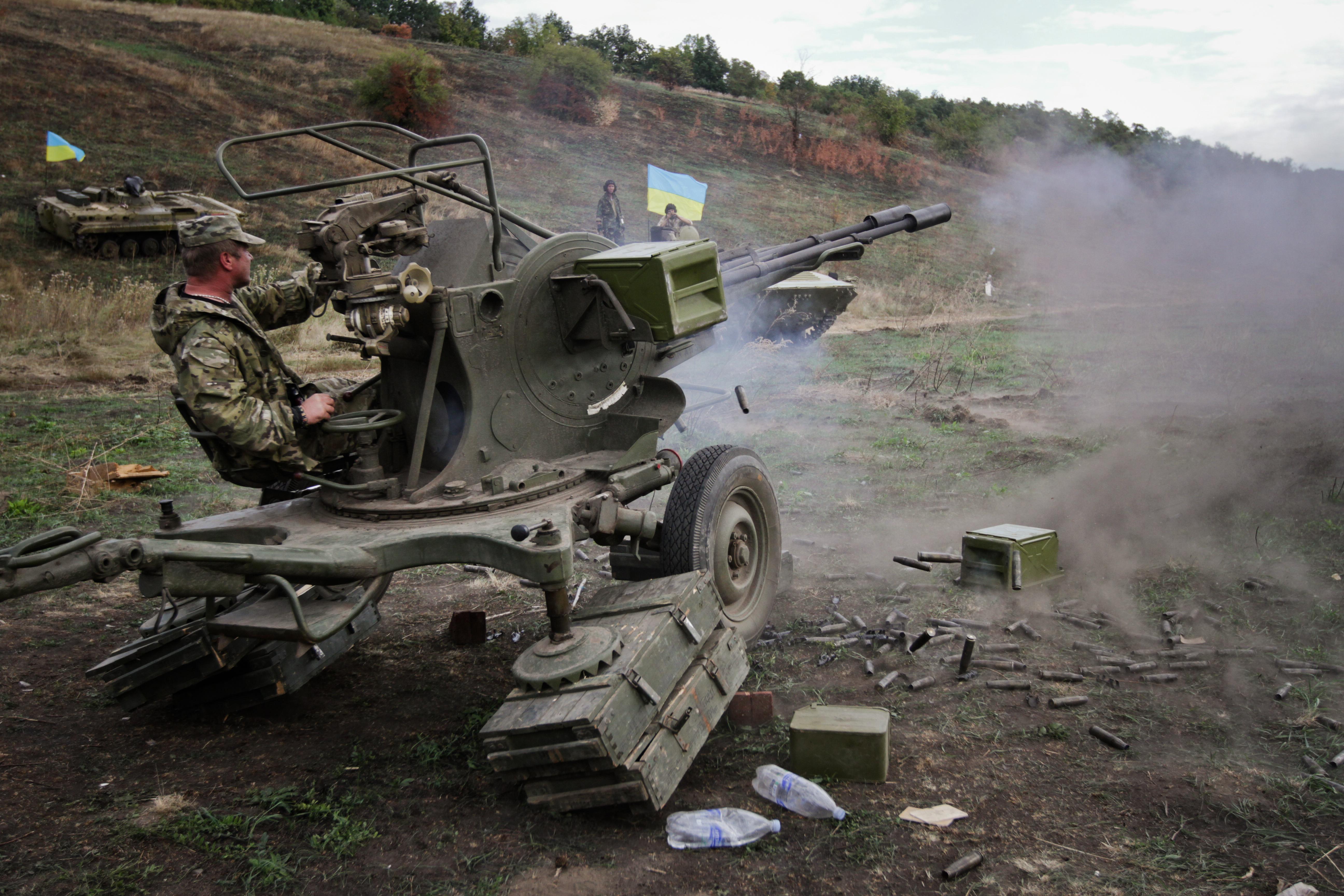Солдат украинской армии ведет стрельбу из автоматической зенитной пушки