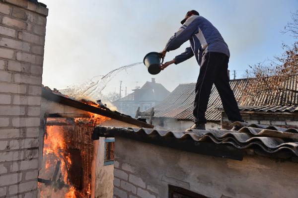 Житель Донецка тушит горящий дом, пострадавший от артобстрела украинскими силовиками