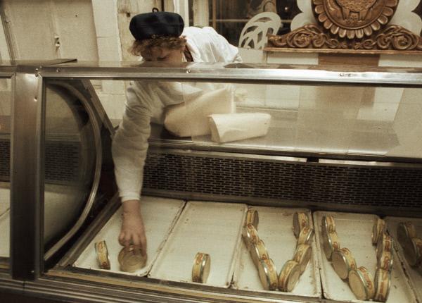 Продавщица продовольственного магазина выкладывает консервные банки на витрину во время тотального дефицита товаров в СССР в начале 90-х годов