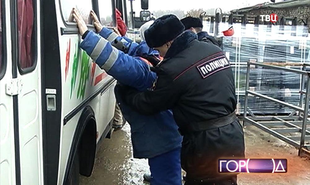 Полицейский проводит обыск задержанных мигрантов