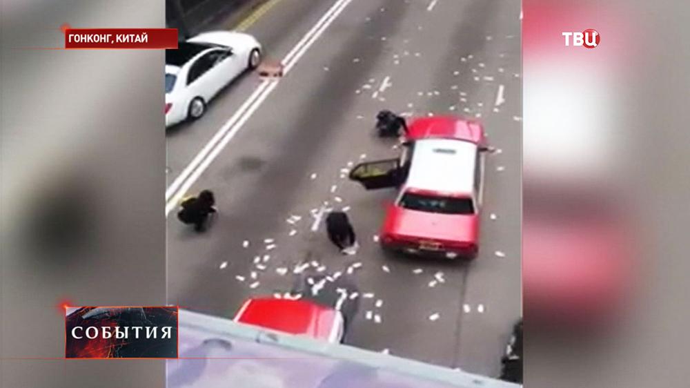 Люди в Гонконге собирают вылетевшие деньги из перевернувшегося инкассаторского фургона