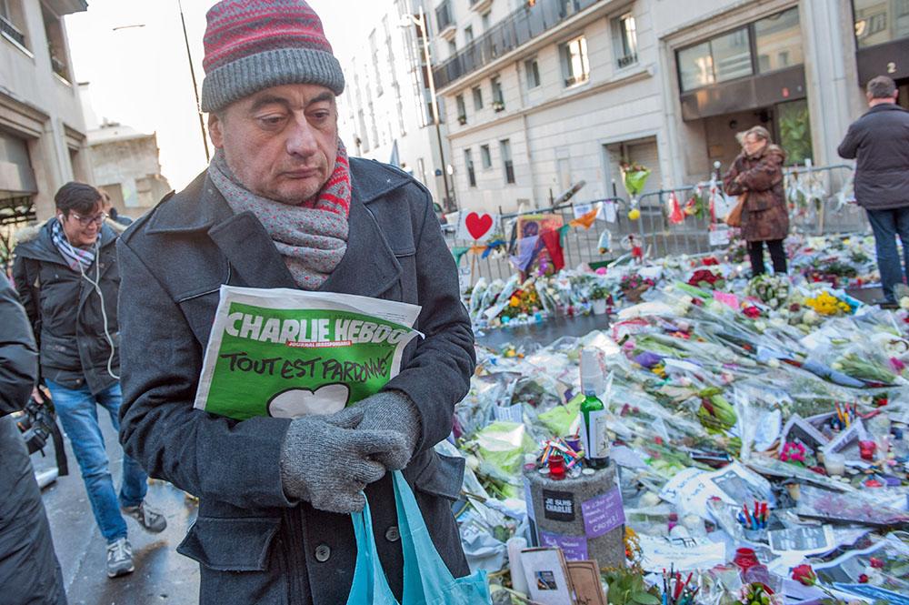 Житель Парижа на месте терракта с номером еженедельника Charlie Hebdo