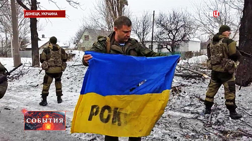 Александр Захарченко держит трофейный украинский флаг