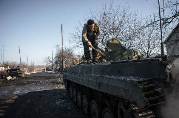 Ополченец ДНР очищает БМП от осколков