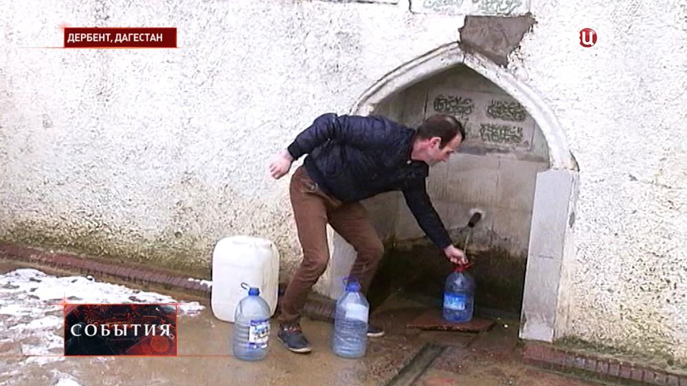 Набирает воду из источника в Дербенте