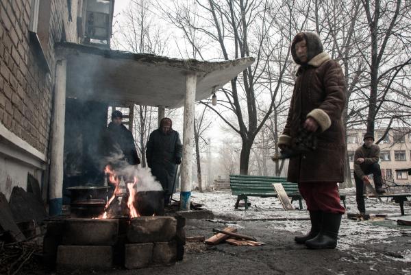 Жители города Дебальцево готовят еду на костре у подъезда многоквартирного жилого дома