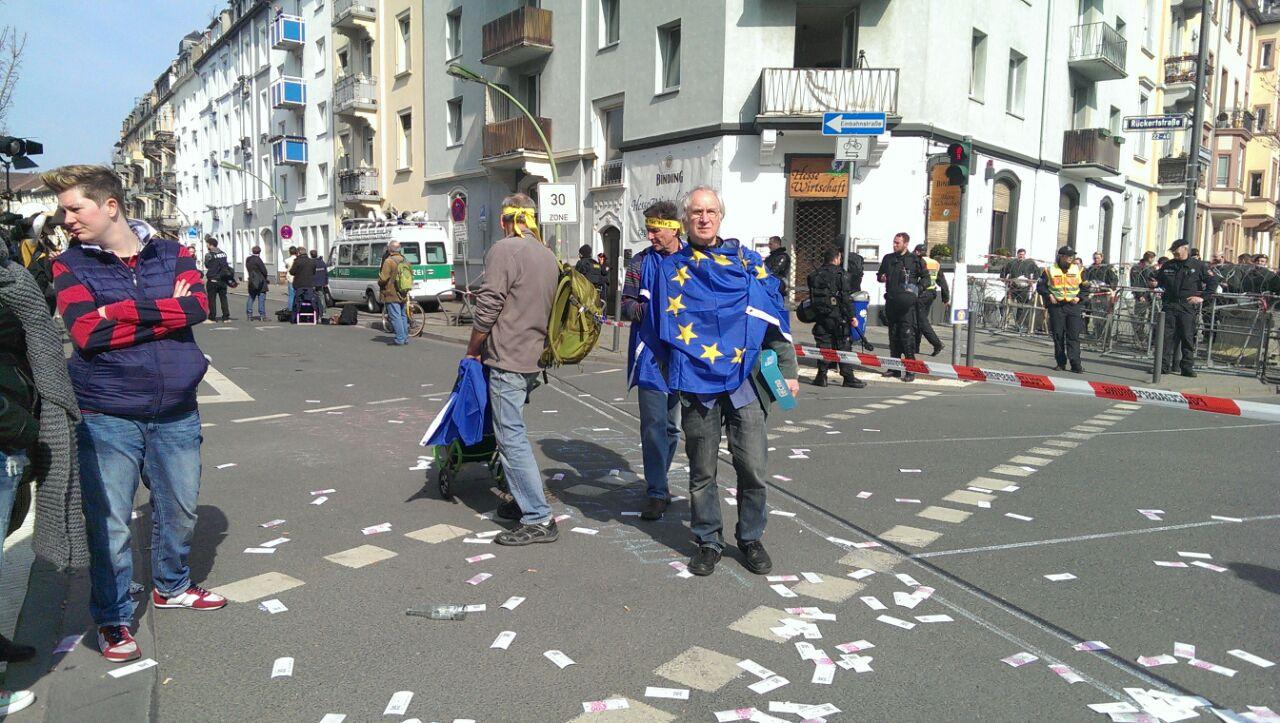 Протестующий, обернутый во флаг Евросоюза, во Франкфурте-на-Майне