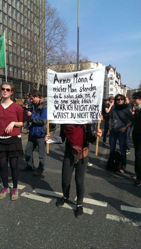 """Плакат митингующего со стихотворением: """"Бедный мужчина встретился с богатым и сказал: не был бы я бедным, не был бы ты богатым"""""""
