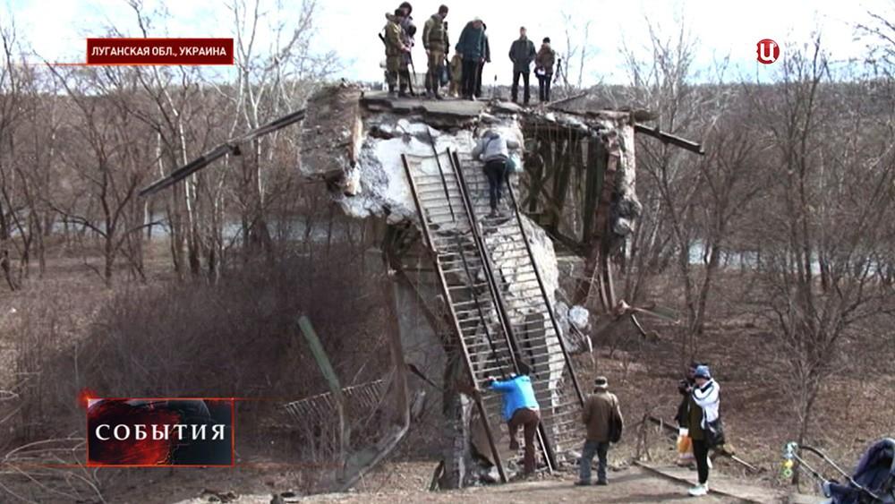 Жители Луганской области поднимаются по разрушенному мосту