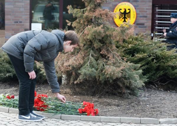 Мужчина возлагает цветы у посольства Германии