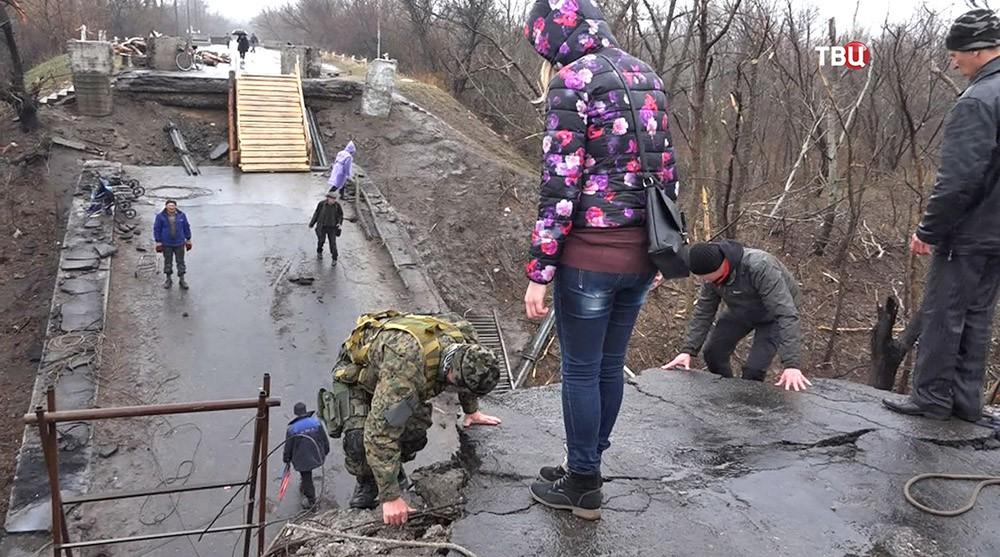 Ополченцы помогают жителям Луганской области спуститься с разрушенного моста