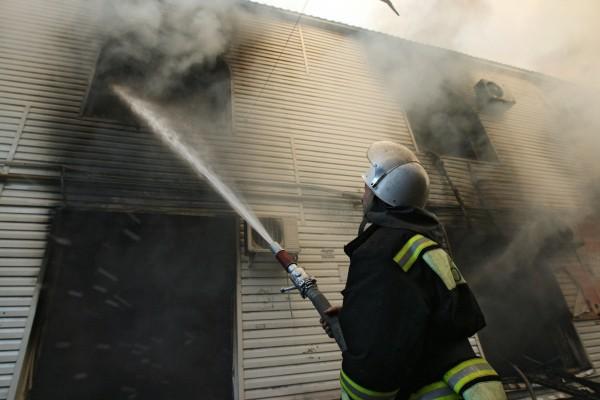 Сотрудник пожарной службы МЧС во время тушения пожара