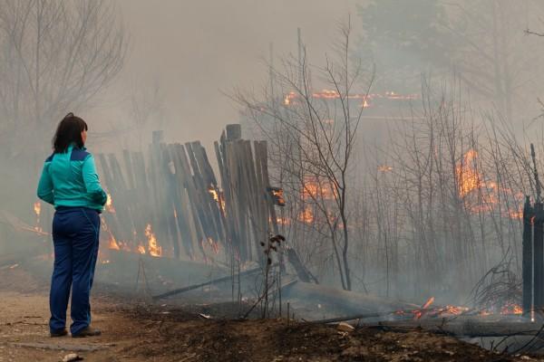 Женщина наблюдает за пожаром на окраине города Абакана