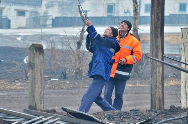 Рабочие меняют линии электропередач после природных пожаров