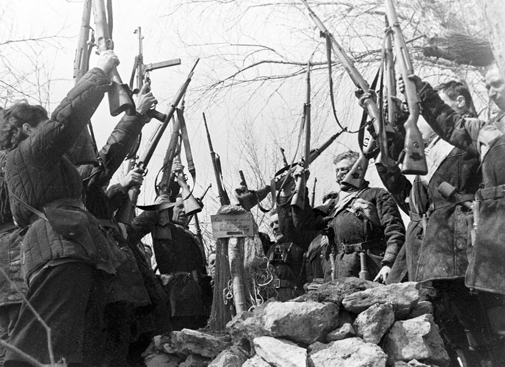 Партизаны клянутся отомстить за убитого фашистами товарища, стоя у его могилы