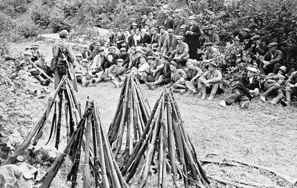 Бойцы партизанского отряда отдыхают, рядом стоят составленные в пирамиды винтовки