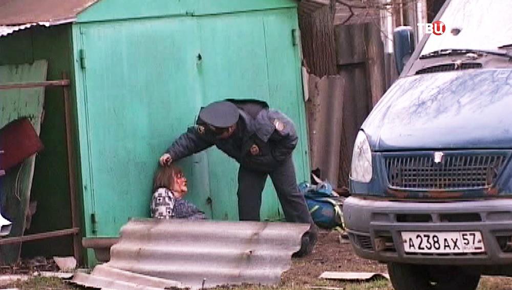 Полицейский осматривает пострадавшую при взрыве в Орле