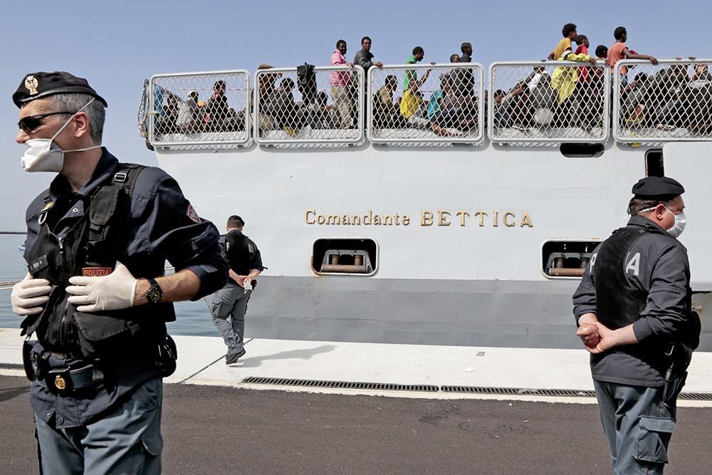 Итальянские полицейские и задержанные мигранты