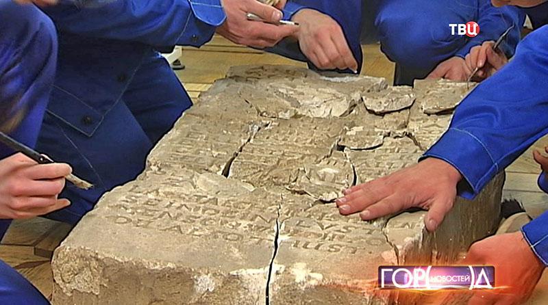 Археологи изучают плиту