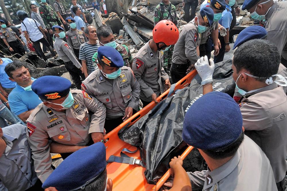 Вынос тел погибших с места крушения самолета в Индонезии