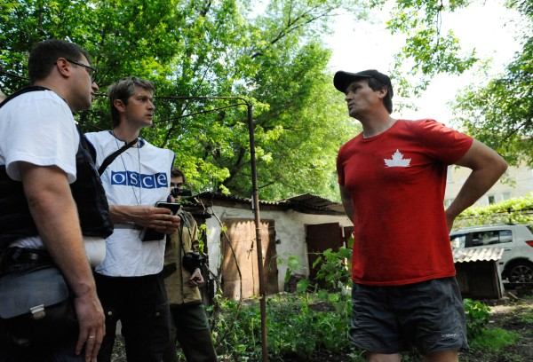Представители ОБСЕ разговаривают с жителем Донецка